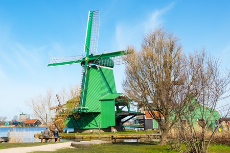 zaanse: Zaanse schans, Netherlands - April 1, 2016: Green windmill in Zaanse Schans, North Holland, traditional village, tourists, blue sky