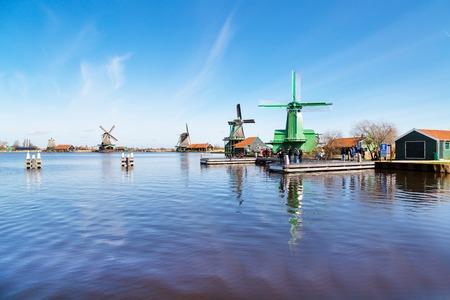 zaandam: Zaanse schans, Netherlands - April 1, 2016: Windmills panorama  in Zaanse Schans, North Holland, traditional village, tourists, blue sky Editorial
