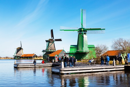 zaanse: Zaanse schans, Netherlands - April 1, 2016: Windmills in Zaanse Schans, North Holland, traditional village, tourists, blue sky