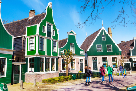 north holland: Zaanse schans, Netherlands - April 1, 2016: Zaanse Schans, traditional village, tourists walking, North Holland, green houses against blue cloudy sky Editorial