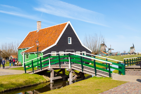 north holland: Zaanse schans, Netherlands - April 1, 2016: Zaanse Schans, North Holland, traditional village, tourists, green houses and windmills against blue cloudy sky Editorial