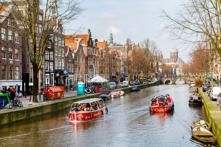 Amsterdam, Netherlands - March 31, 2016: Cruise boat at Amsterdam canals in Holland, bridge, people and street view Editorial