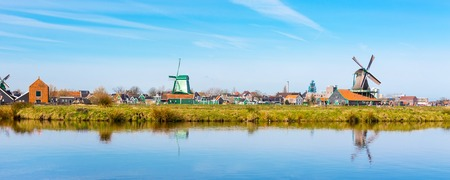 Panoramic view of windmill in Zaanse Schans, traditional village in Holland, reflection in lake, blue sky, copy space