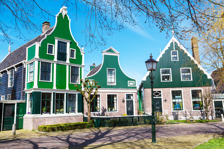 north holland: Zaanse Schans, traditional village, North Holland, green houses against blue cloudy sky