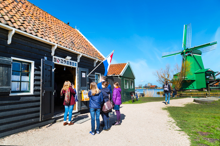 schans: Zaanse schans, Netherlands - April 1, 2016: Green windmill in Zaanse Schans, Holland, traditional village, tourists near Cacaolab shop, blue sky