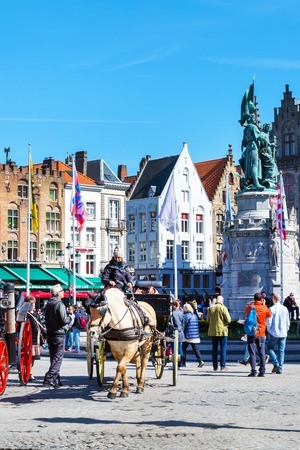 hackney carriage: Bruges, Belgium - April 10, 2016: Market place or Grote Markt square with colorful traditional houses, fiaker, people in popular belgian destination