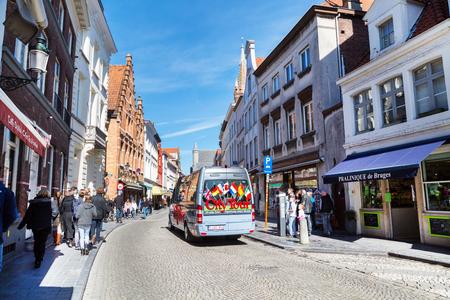 bruges: Bruges, Belgium - April 10, 2016: Colorful Hop on hop off Sightseeing Tours bus in Bruges street