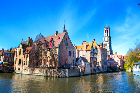 belfort: Bruges, Belgium - April 10, 2016: Scenic cityscape with medieval houses and tower Belfort and canal in Bruges, Belgium