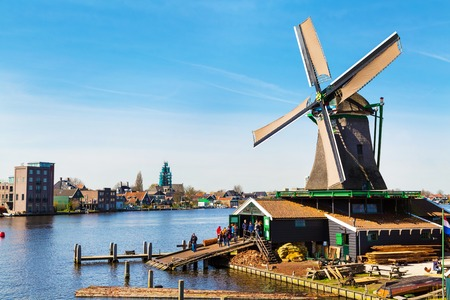 zaanse: Zaanse schans, Netherlands - April 1, 2016: Windmill in Zaanse Schans, North Holland, traditional village, tourists, blue sky Editorial