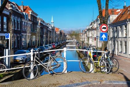 Delft, Nederland - 8 april 2016: Kleurrijke uitzicht op straat met de traditionele Nederlandse huizen, fietsen, gracht in het centrum van de populaire bestemming Holland