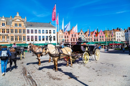 hackney carriage: Bruges, Belgium - April 10, 2016: Market place or Grote Markt square with colorful traditional houses, fiaker, people walking in popular belgian destination Editorial