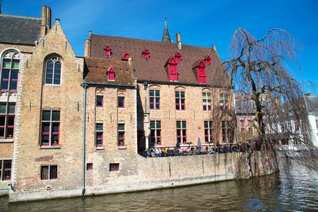 canal house: Bruges, Belgium - April 10, 2016: Scenic cityscape with medieval house, cafe and canal in Bruges, Belgium