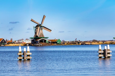 zaanse: Zaanse schans, Netherlands - April 1, 2016: Windmills panorama in Zaanse Schans, North Holland, traditional village, tourists, blue sky Editorial