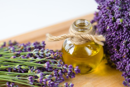 Fresh lavender flowers and bottle of oil on wooden background