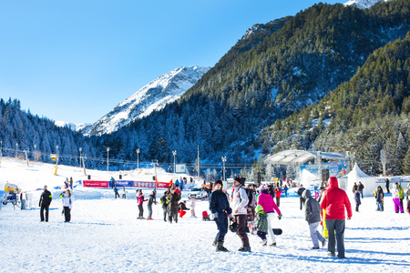 ski walking: Bansko, Bulgaria - December, 12, 2015: Vibrant image of ski resort Bansko, Bulgaria, pistes and mountain with pine trees, ski slope, people walking and skiing