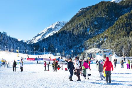 Bansko, Bulgaria - December, 12, 2015: Vibrant image of ski resort Bansko, Bulgaria, pistes and mountain with pine trees, ski slope, people walking and skiing
