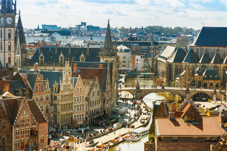 Ghent, Belgium - April 12, 2016: Aerial panoramic cityscape view of Ghent, Belgium with St. Michael Bridge, canal, traditional medieval houses, church against cloudy blue sky Editorial