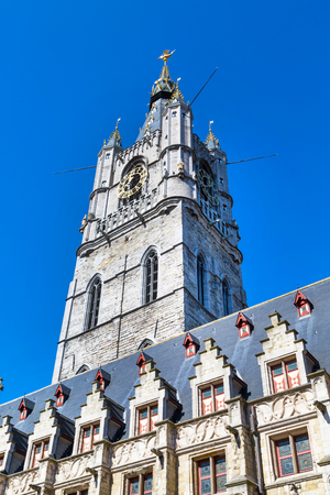 Grand Belfry with clock in Ghent, Belgium close up on blue sky background