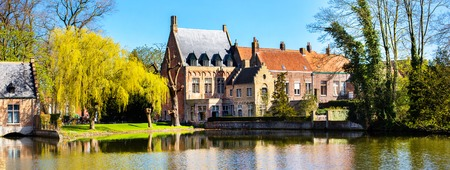 Bruges, Belgium panorama with lake and medieval houses against blue sky Stock Photo