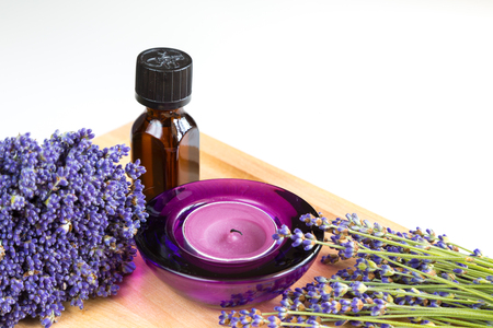 tea candle: Tea candle, oil and lavender flowers on table close up Stock Photo