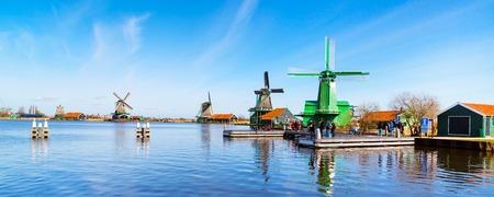 Zaanse Schans, Nederland - 1 april 2016: Windmolens panorama in de Zaanse Schans, Noord-Holland, traditioneel dorp, toeristen, blauwe hemel