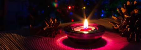 tea candle: Christmas holiday panoramic background with purple tea candle and colorful lights of Christmas tree,copyspace