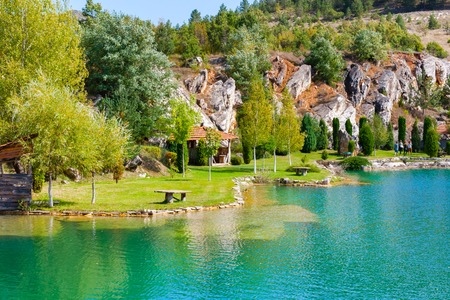 Lake with turquoise water and green trees landscape in the mountains. Eco park background