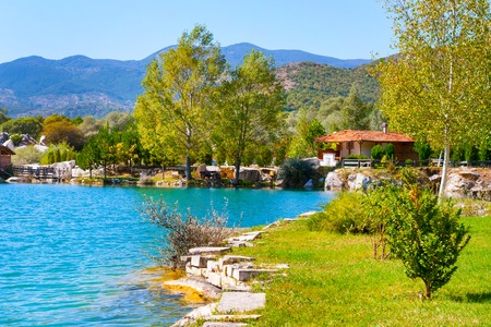 Lake with turquoise water, green trees and red roof house landscape. Eco park background