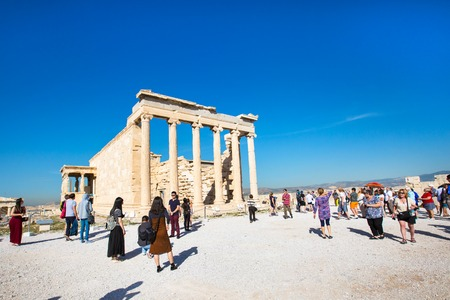 Athens, Greece - October 14, 2016: Tourists near Erechtheum temple ruins decorated with Caryatids female statues in Acropolis Editorial