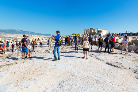 Athens, Greece - October 14, 2016: Tourists taking photos near temple ruins in Acropolis, Athens