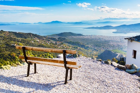 Bench overlooking Volos city and sea gulf aerial view from Pelion mount, Greece