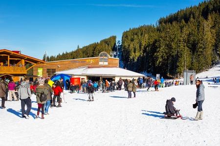 station ski: Bansko, Bulgaria - December 12, 2015: Bunderishka polyana, ski station, cable car lift, Bansko, Bulgaria,  blue cabins and mountain with pine trees, people Editorial