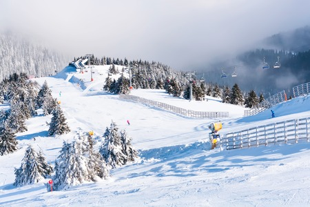 ski lift: Ski resort, ski slope, ski lift, pine trees and fog mountains panorama