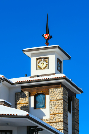 close up chalet with clock tower against blue sky in bulgarian ski resort Bansko, Bulgaria