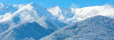 ski slopes: travel ski resort background with ski slopes panoramic view, snow mountain peak, fog and blue sky