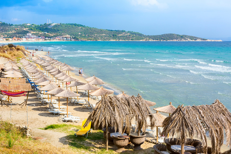 Summer greek beach vacation panoramic background with turquoise sea water waves and umbrellas, Greece Фото со стока