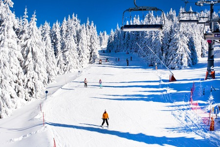 ski walking: Ski resort, slope, ski lift, skiers on the piste among white snow pine trees forest