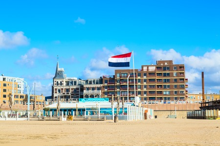 scheveningen: Scheveningen, Netherlands - April 7, 2016: Scheveningen beach panorama with dutch flag, houses near Hague, Holland