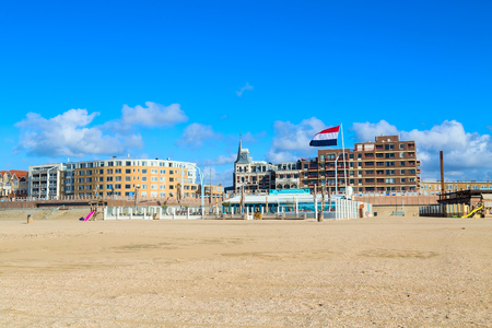 Scheveningen, Netherlands - April 7, 2016: Scheveningen beach panorama with dutch flag, houses near Hague, Holland