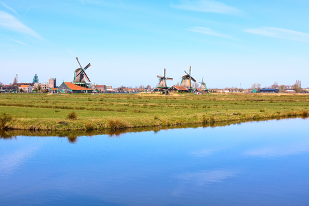 zaandam: Panoramic view of windmills in Zaanse Schans, traditional village in Holland, lake, blue sky, copy space