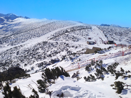 ski slopes: Panorama of winter mountains over the clouds, ski slopes in bulgarian alpine ski resort Borovets Stock Photo
