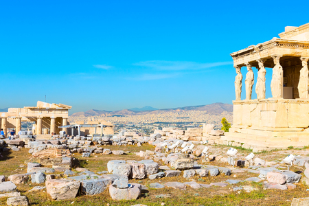background with Acropolis, porch of caryatids, Erechtheum Temple in Athens, Greece and blue sky