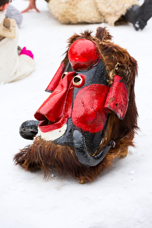Masks of bulgarian traditional carnival kuker costume in the snow