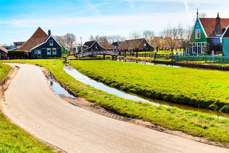Zaanse Schans, traditional village, tourists walking, North Holland, green houses against blue cloudy sky
