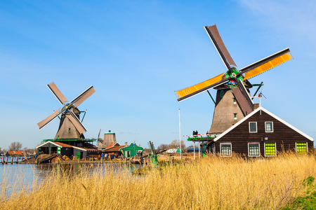Panoramic view of windmills in Zaanse Schans, traditional village in Holland, lake, blue sky