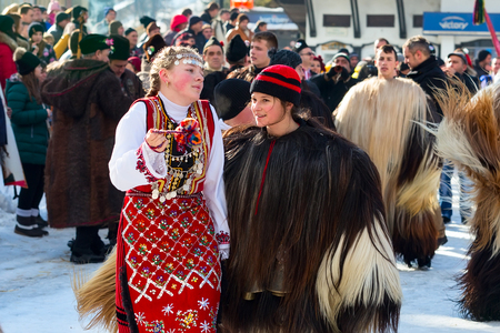 bulgaria girl: Razlog, Bulgaria - January 14, 2017: Girls in traditional carnival kuker costumes at Kukeri festival Starchevata Editorial
