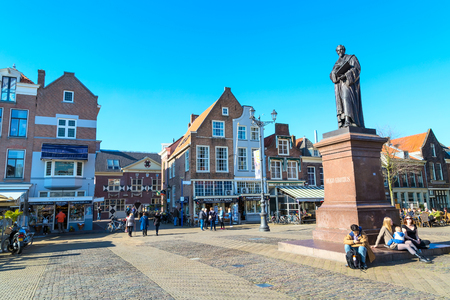 Delft, Netherlands - April 8, 2016: Statue of Hugo Grotius, traditional dutch houses, people walking in downtown of popular Holland destination Editorial