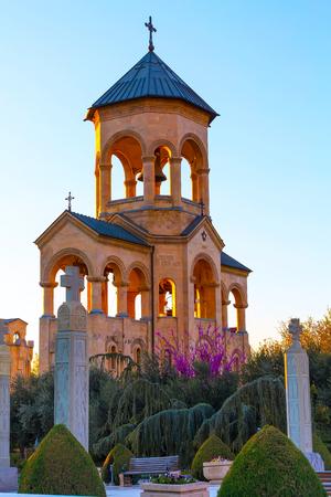 misterious: Bell tower near Holy Trinity church or Tsminda Sameba Cathedral sunset panorama in Tbilisi, Georgia Stock Photo