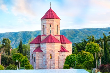 misterious: Chapel near Holy Trinity church or Tsminda Sameba Cathedral with colorful clouds in Tbilisi, Georgia Stock Photo