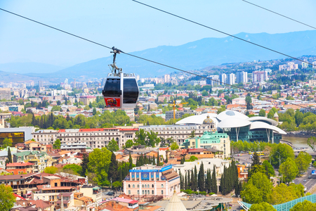 Tbilisi, Georgia - April 29, 2017: Tbilisi red cable car cabins and aerial city skyline panoramic view Banco de Imagens - 79366055